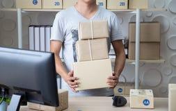 La PME, caja de la tenencia del vendedor de la pequeña empresa se prepara para enviado al cliente fotos de archivo
