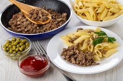 La poêle avec frit hachent, roulent avec des pâtes, pois, le ketchup, plat avec des macaronis, l'hachis de fruits secs frit, four photographie stock libre de droits