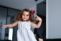 La poca ragazza di sorrisi con un fiore in suoi capelli fotografia stock