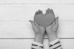 La poignée d'amour, se ferment  Mains femelles tenant le coeur de papier rouge, vue supérieure Photographie stock libre de droits