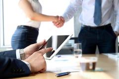 La poignée de main d'associés au-dessus des affaires objecte sur le lieu de travail Femme d'affaires travaillant avec la tablette Photographie stock