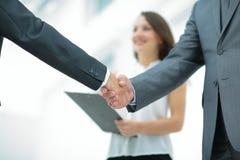 La poignée de main de deux hommes d'affaires à l'arrière-plan des experts font Image stock