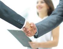 La poignée de main de deux hommes d'affaires à l'arrière-plan des experts font Images stock