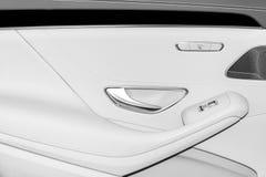 La poignée de porte avec le siège de puissance et la fenêtre commandent des boutons d'une voiture de tourisme de luxe Intérieur d Photographie stock
