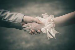 La poignée montre que l'amour entre les jeunes mariés marchera loin avec une compréhension et pour toujours Image stock