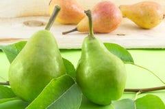 La poire verte et la poire s'embranchent sur une table en bois avec les poires oranges Image libre de droits