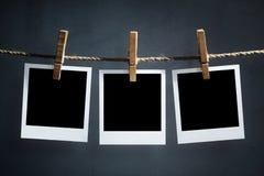 La polaroid en blanco fotografía la ejecución en una cuerda para tender la ropa imagenes de archivo