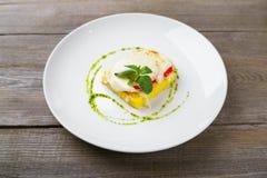 La polenta al forno con formaggio, il pomodoro ed il pesto sauce immagini stock