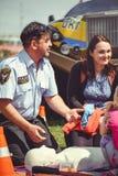 La policía está entrenando a los primeros auxilios para la gente en un maniquí en el centro de ciudad, una acción de los primeros Fotografía de archivo libre de regalías