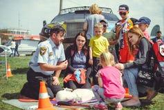 La policía está entrenando a los primeros auxilios para la gente en un maniquí en el centro de ciudad, una acción de los primeros Foto de archivo libre de regalías