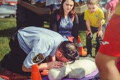 La policía está entrenando a los primeros auxilios para la gente en un maniquí en el centro de ciudad, una acción de los primeros Foto de archivo