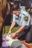 La policía está entrenando a los primeros auxilios para la gente en un maniquí en el centro de ciudad, una acción de los primeros Imagenes de archivo