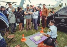 La policía está entrenando a los primeros auxilios para la gente en un maniquí en el centro de ciudad, una acción de los primeros Fotografía de archivo