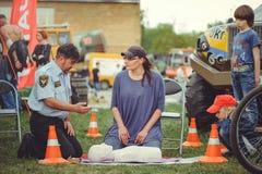 La policía está entrenando a los primeros auxilios para la gente en un maniquí en el centro de ciudad, una acción de los primeros Fotos de archivo
