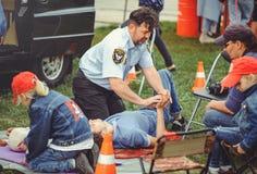 La policía está entrenando a los primeros auxilios para la gente en un maniquí en el centro de ciudad, una acción de los primeros Imagen de archivo