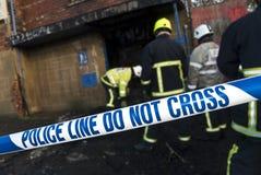 La policía sujeta con cinta adhesiva en la escena del fuego Foto de archivo