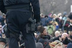 La polizia con la pistola custodice la folla Immagini Stock