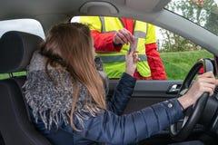 La polizia controlla la licenza di una giovane donna nell'automobile fotografia stock