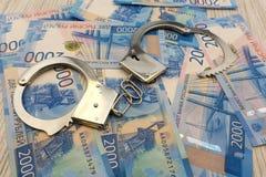 La polizia d'acciaio ammanetta la menzogne sui precedenti dei dollari con la pila piegata di banconote delle rubli russe fotografie stock libere da diritti