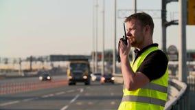 La polizia stradale con il walkie-talkie lavora alla strada principale archivi video