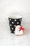 La polka noire a pointillé la tasse de café avec un biscuit fait maison en forme de coeur au-dessus du fond en bois blanc Photographie stock libre de droits