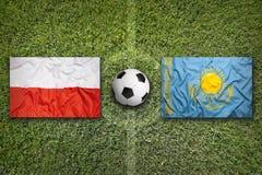 La Polonia contro Bandiere del Kazakistan sul campo di calcio Fotografia Stock