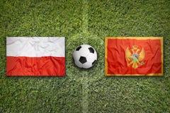 La Polonia contro Bandiere del Montenegro sul campo di calcio Fotografia Stock
