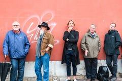 LA POLONIA, CRACOVIA, 16 07 2017 Cinque uomini differenti che stanno vicino al rosso fotografia stock