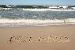 La Polonia - nome di paese dissipato su una spiaggia Immagini Stock Libere da Diritti