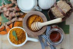 La polvere della curcuma con miele ed il latte per sfregano Immagini Stock