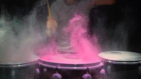 La polvere rossa di holi rimbalza fuori dal tamburo nel modello di onda d'urto, movimento lento Priorità bassa nera stock footage