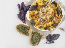 La pomme de terre coupée en tranches a fait cuire au four avec du fromage et le basilic dans le four Photographie stock