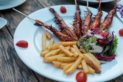 La pomme de terre fait frire avec des crevettes roses de friture, salade de laitue Au-dessus du fond en bois Photographie stock libre de droits