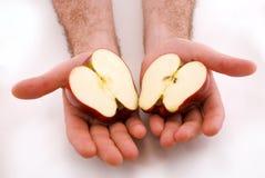 la pomme divise en deux les mains deux Image libre de droits