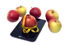 La pomme mûre, les échelles de cuisine et la bande de mesure ont isolé le plan rapproché Photographie stock