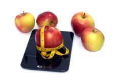 La pomme mûre, les échelles de cuisine et la bande de mesure ont isolé le plan rapproché Image libre de droits
