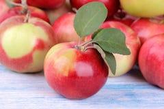 la pomme rouge avec le vert laisse le plan rapproché sur la table en bois bleue photos stock