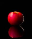 La pomme rouge fraîche avec des gouttelettes de l'eau contre la réflexion noire de fond laisse tomber le mouvement frais d'action Photos stock