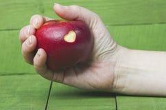 La pomme rouge fraîche avec un coupe-circuit en forme de coeur chez la main de la femme courtisent dessus Photos libres de droits