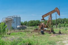La pompa funzionante solleva il petrolio con il crick greggio di pompaggio al sito di trivellazione petrolifera in rura Immagini Stock