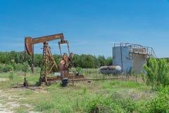 La pompa funzionante solleva il petrolio con il crick greggio di pompaggio al sito di trivellazione petrolifera in rura Fotografia Stock Libera da Diritti