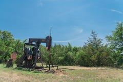 La pompa funzionante solleva il petrolio con il crick greggio di pompaggio al sito di trivellazione petrolifera in rura Fotografia Stock
