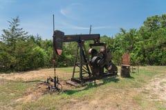 La pompa funzionante solleva il petrolio con il crick greggio di pompaggio al sito di trivellazione petrolifera in rura Immagine Stock