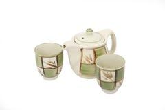 La porcellana ha decorato la teiera e due tazze su bianco Immagine Stock