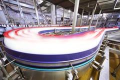 La porción de botellas de leche se mueve rápidamente a través de tubería Imágenes de archivo libres de regalías