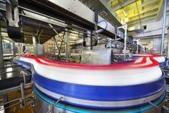 La porción de botellas de leche se mueve a través de tubería larga Imagen de archivo libre de regalías