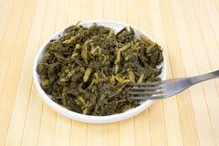 La porción de la col com n se pone verde en un plato con la bifurcación fotos de archivo