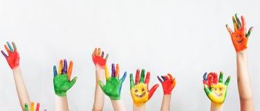 La porción de manos pintadas aumentó para arriba, el día de los niños Foto de archivo libre de regalías