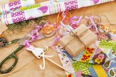 La porción de materia para los regalos hechos a mano, tijeras, cinta, papel con el modelo del campo, alista para el concepto del  Imágenes de archivo libres de regalías