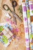 La porción de materia para los regalos hechos a mano, tijeras, cinta, papel con el modelo del campo, alista para el concepto del  Fotografía de archivo